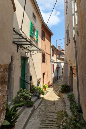 Apartment houses and footpath in the town of Vrbnik on the island of Krk, old historical buildings in summer, Croatia Europe