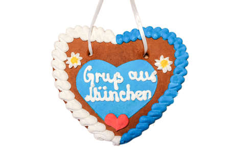 Gingerbread heart with written slogan: Greetings from Munich, Bavarian symbol and Munich landmark, Gingerbread candy isolated on white background, Bavaria Germany Europe