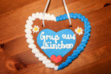 Gingerbread heart with written slogan: Greetings from Munich, Bavarian symbol and Munich landmark, Gingerbread candy on wooden background, Bavaria Germany Europe