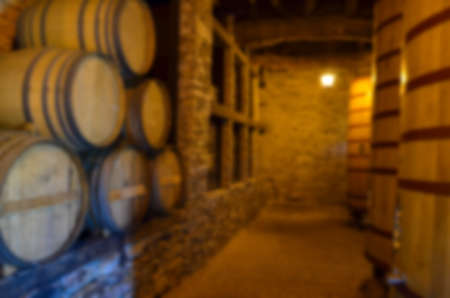 Red wine tasting in an old wine cellar with wooden wine barrels in a winery, Soft focus effect