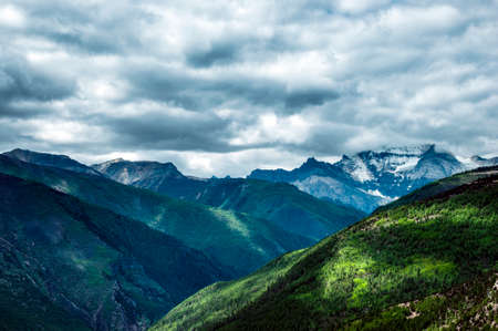 the snowy mountains: Snowy mountains with clouds covered Stock Photo