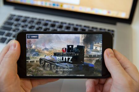 Moscow / Russia - February 20, 2019: holding an iPhone on MacBook background. World of tanks game is loading