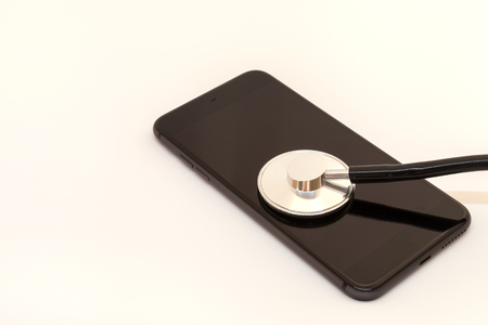 stethoscope is leaning against the screen of a black smartphone