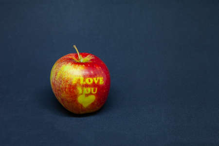 whole red apple on a black background with the words i love you
