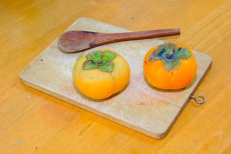 trencher: Two persimmon and Wood Spoon on the chopping block