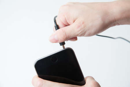 earphone: putting earphone jack to smartphone Stock Photo