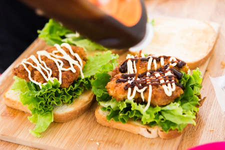 sandwitch: putting sauce on chicken cutlet sandwitch