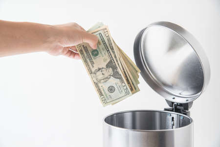 throwing away dollar in trashcan