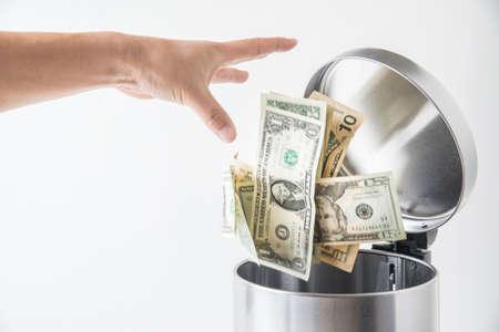trashcan: throwing away dollar in trashcan