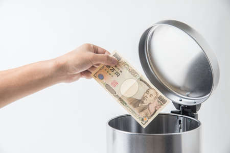 throwing away japanese yen  in trashcan Stok Fotoğraf