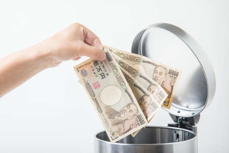 throwing away japanese yen  in trashcan 写真素材