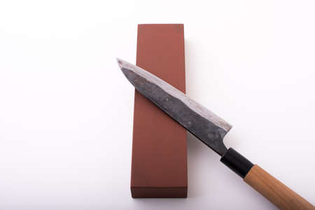 sharpening japanese knife with grindstone 免版税图像