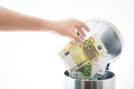 throwing away euro in waste can Stockfoto