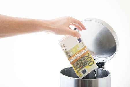 throwing away euro in waste can Standard-Bild