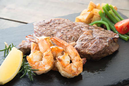 rib eye steak and grilled shrimp on black plate