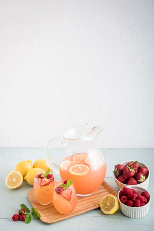pink berry lemonade with strawberry and orange on the table closeup photo