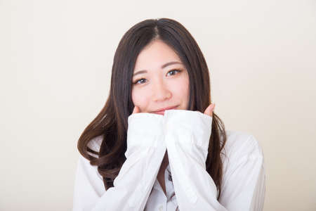 young asian woman covering mouth with sleeves