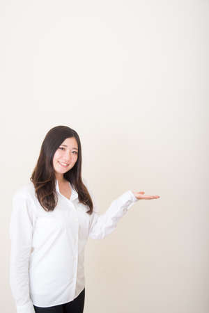 young asian woman introducing with hand