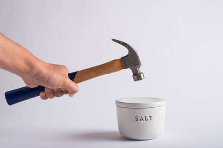 destroying salt container with hammer