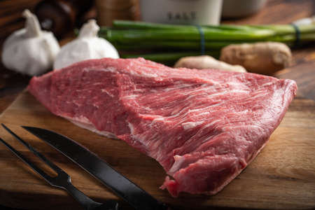 raw tri tip steak beef on wooden cutting board