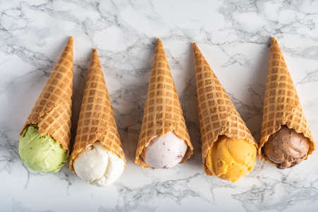 assorted ice creams in waffle cone on marble background Stockfoto