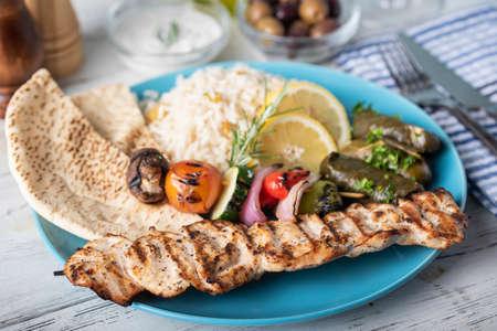 assorted greek food platter with souvlaki, rice, pita and dolmades