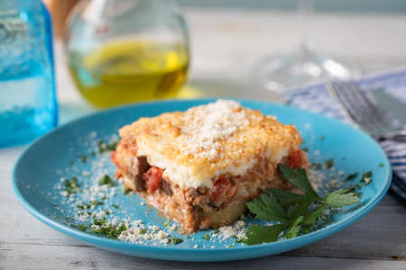 greek moussaka on blue plate in white wooden background