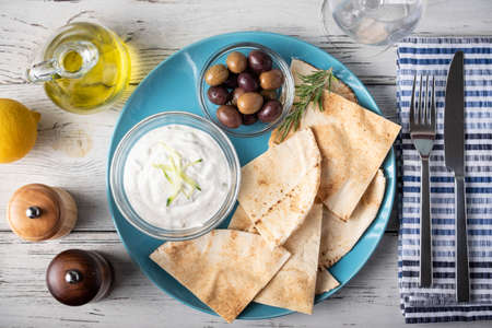 tzatziki with pita bread on blue plate