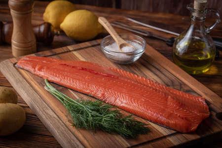 Filete de salmón crudo entero sobre tabla de cortar de madera
