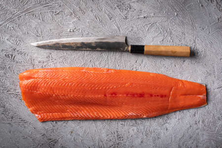 whole raw salmon fillet with japanese sushi knife