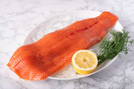 whole raw salmon fillet on marble background
