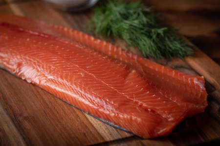 whole raw salmon fillet on wooden cutting board