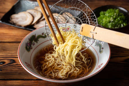 putting japanese ramen noodle in soy sauce chicken broth