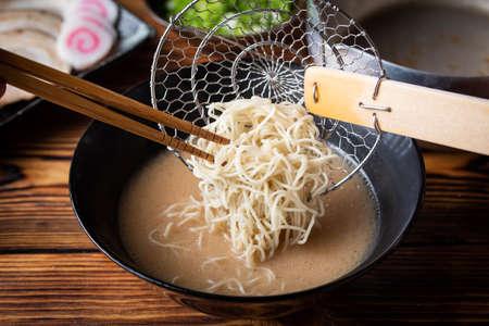 putting japanese ramen noodle in pork bone broth