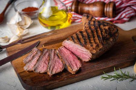 sliced tri tip seak marinated with santa maria sauce on wooden cutting board