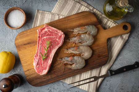 raw new york strip steak and prawn, surf and turf preparation Imagens