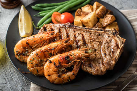 surf and turf, new york strip steak and grilled prawn Imagens