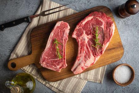 raw beef steak, new york strip steak and ribeye