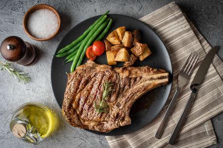 ribeye steak on black plate, concrete background