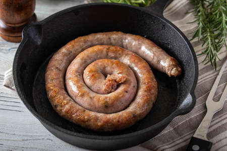cooked coiled sausage on cast iron pan
