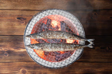grilling japanese saury on charcoal grill