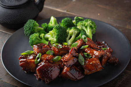 teriyaki chicken and broccoli on black plate