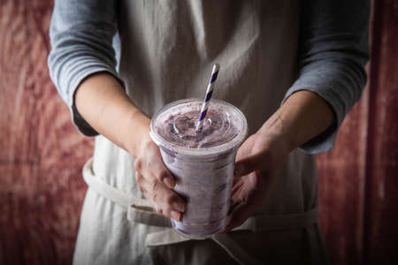 female with apron giving berry smoothie in plastic cup