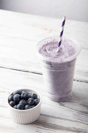 blueberry smoothie in plastic bup on white background