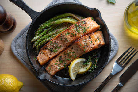 cooked salmon in iron skillet with asparagus