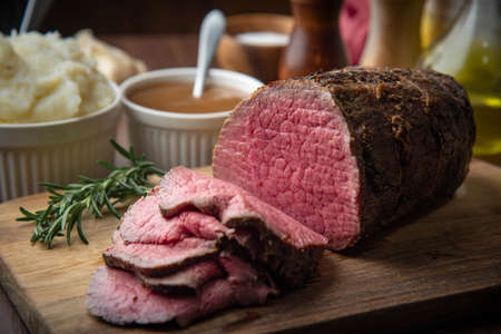 sliced eye of round beef roasted beef on cutting board Stock Photo