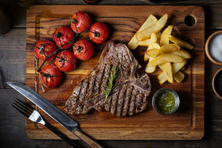 T-bone steak with baked tomato and french fries