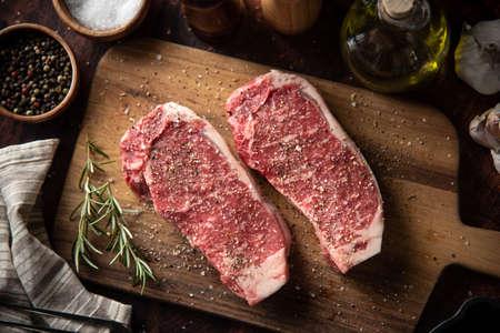 seasoned raw sirloin beef steak on cutting board
