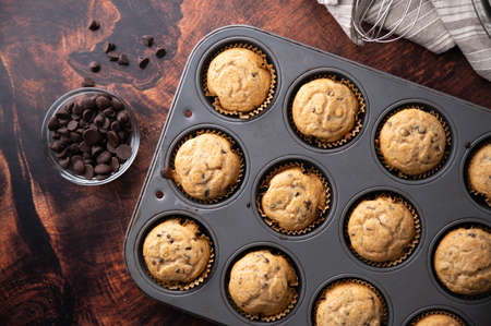 chocolate chip muffin on dark wooden board