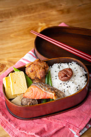 japanese style bento in wooden box with salmon and fried chicken